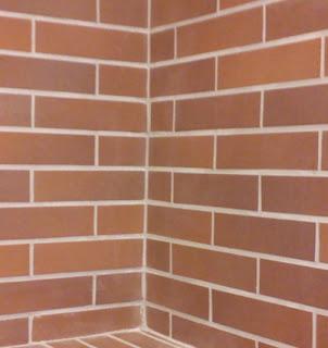 Pink Floyd Another Brick in the Wall dalára emlékeztető vöröstéglás, bezáródó fal, amely az iskola és a tanárok, pedagógusok mátrixát szimbolizálja.