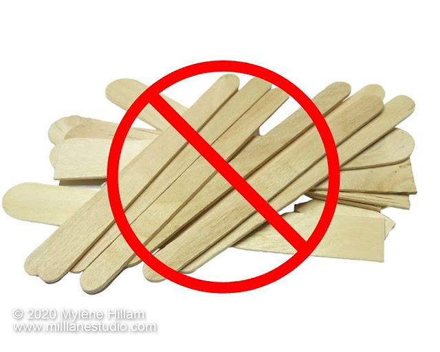 Bundle of wooden popsicle sticks with a red circle and cross overlayed on top