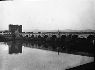 Slightly grainy black and white photograph of a stone bridge over a river. The still water dominates the image and reflects the arches and piers of the bridge which cuts across the centre of the image. There is a square stone tower centre left near the termination of the bridge and misty hills in the distance beyond the bridge.