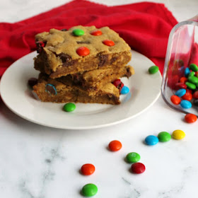 three pieces of chewy salted caramel m&m blondies stacked high on plate with candies scattered around