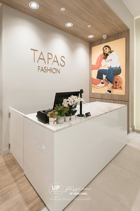 Sunway pyramid tapas fashion cashier counter with wood texture arch and fashion poster lightbox, minimalist and sleek cashier counter in white spray paint and marble top