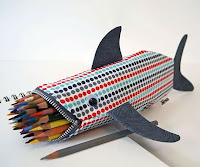 Ağzından birçok renkli kalem çıkan bir köpek balığı şeklinde tasarlanmış fermuarlı bir kalemlik