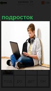 Мальчик подросток сидя на полу с ноутбуком и наушниками слушает музыку