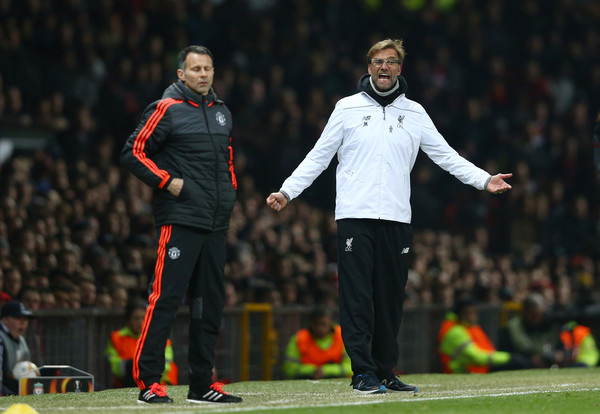 Jurgen Klopp, manager of Liverpool reacts as Ryan Giggs Assistant Manager of Manchester United looks on during the UEFA Europa League round of 16, second leg match between Manchester United and Liverpool at Old Trafford on March 17, 2016 in Manchester, England