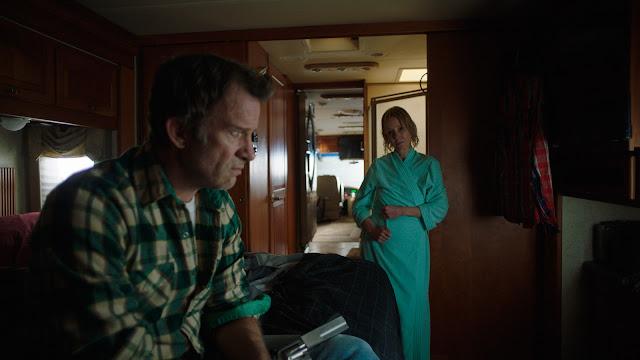 """Na imagem, Paul e Wendy ddentro do trailer, com Wendy de robe tendo acabado de saído do banho e Paul com uma arma de fogo na mão, no canto esquerdo, e Wendy olhando para ele com ares inquisitivos não exatamente no meio nem no canto, mas sim na segunda de """"3 partes"""" do enquadramento."""