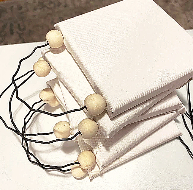 stack of mini canvases with beads and wire