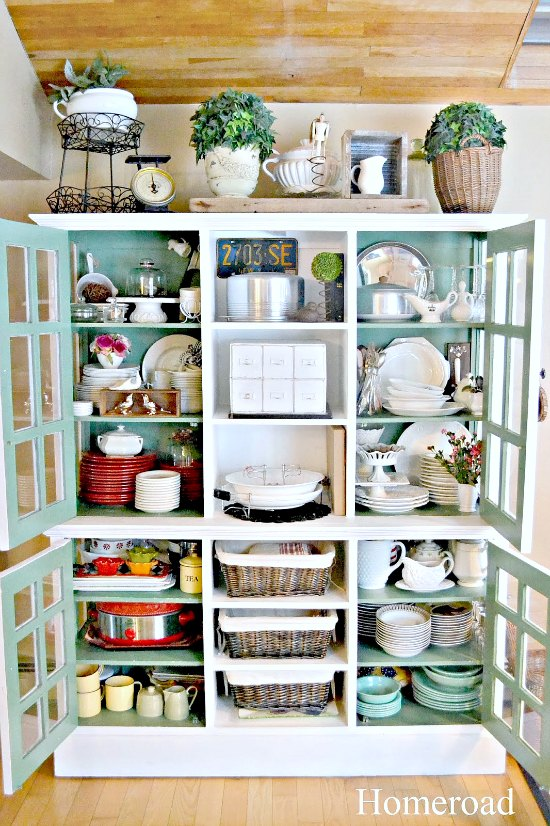 Large hutch with the doors open and packed with dishes