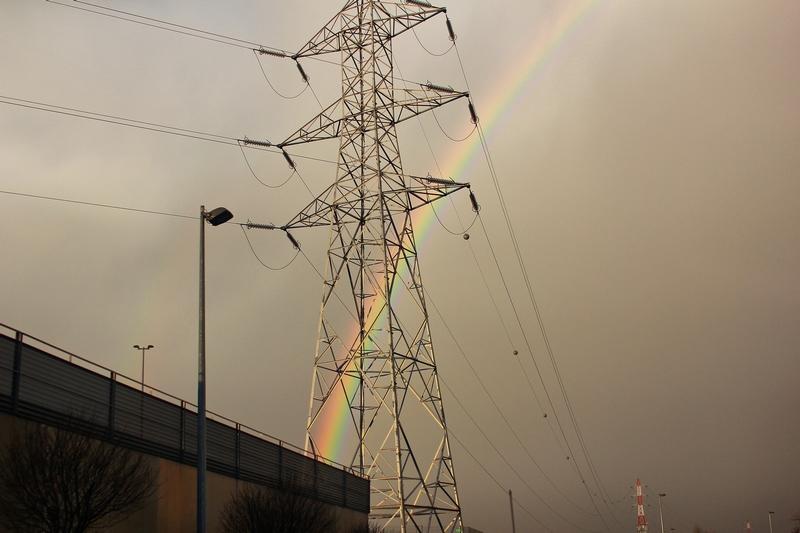 arc-en-ciel passant derrière un pylône dans le parking de l'aéroport de Charleroi en Belgique