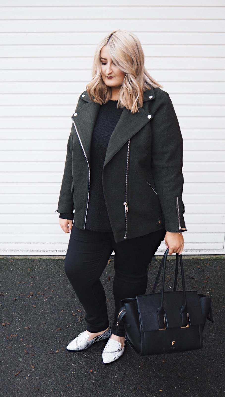 Plus size white woman wearing black jeans, black jumper, khaki River Island biker jacket, ASOS crocodile print loafers with Fiorelli handbag standing against a white wall