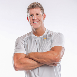 author Joel Marion, a muscular man with short blonde hair smiles while wearing a white athletic shirt against a white background