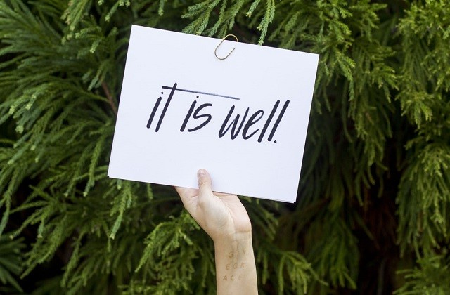 woman's hand holding All Is Well sign against pine leaves