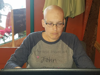 A bald woman sitting in front of an open laptop, looking at the screen in concentration.