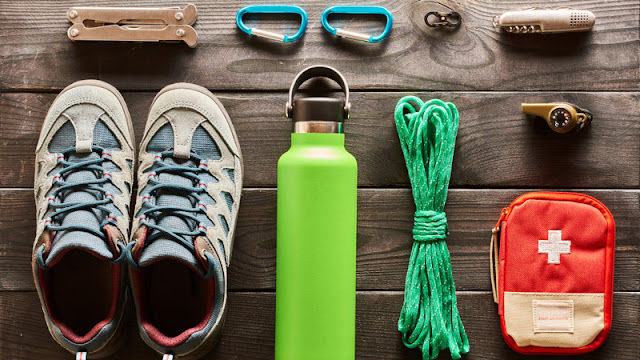 hiking shoes, multitool, first aid kit, water bottle, and rope laid out