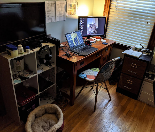 A desk with a laptop and second monitor; to the left shelving unit with TV atop it and to the right the desk, a small filing cabinet.