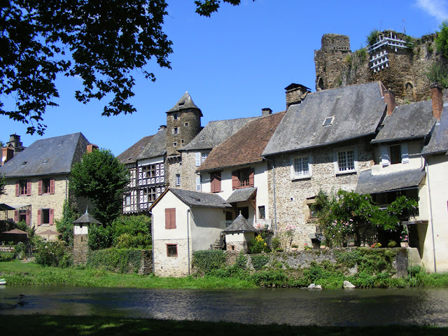 Looking across the river from the park to the chateau ruins and houses in between. Ségur le Chateau, Correze, France. Photo by Loire Valley Time Travel.