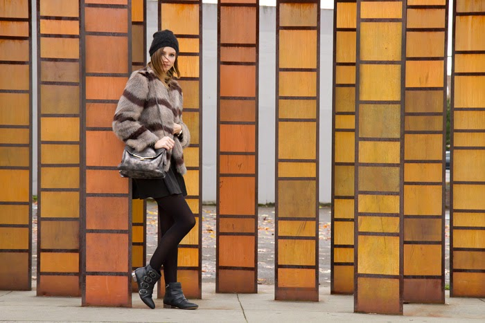 Vancouver Fashion Blogger, Alison Hutchinson, is wearing a striped faux fur coat from Nordstrom, an In Love With Fashion black dress, sam edelman buckle boots, a silver botkier bag and a slouchy beanie.