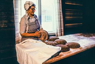 Nainen raidallisessa essussa käsittelee ruisleipiä pöydällä. Takana ikkuna.