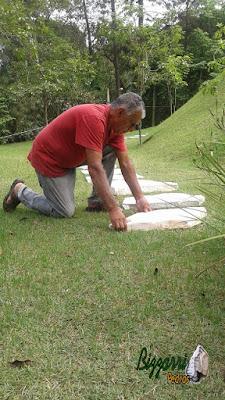 Bizzarri, da Bizzarri Pedras, trabalhando, iniciando a execução dos caminhos de pedra no jardim sendo o tipo de caminho com pedra com junta de grama em casa em condomínio em Mairiporã-SP.