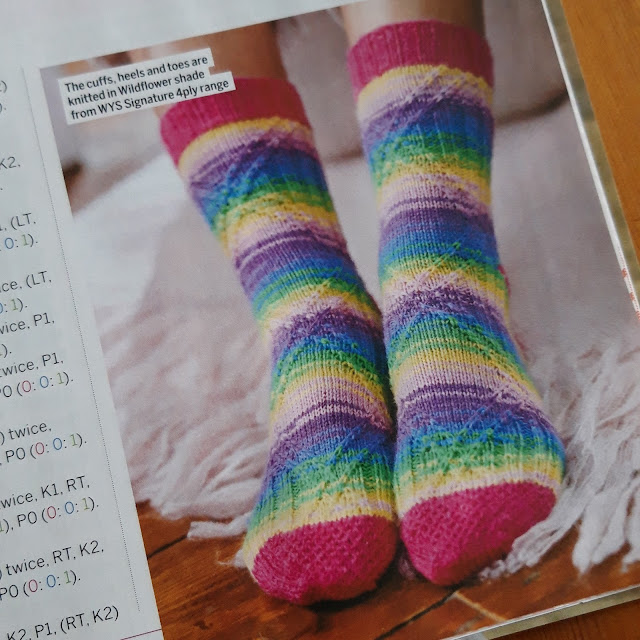 A photo of a pair of socks knitted in Winwick Mum wildflower yarn (blue, yellow, green, pink, purple) with a diamond textured pattern