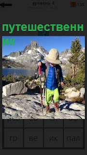 Маленький путешественник в панаме с альпенштоком смело шагает по камням