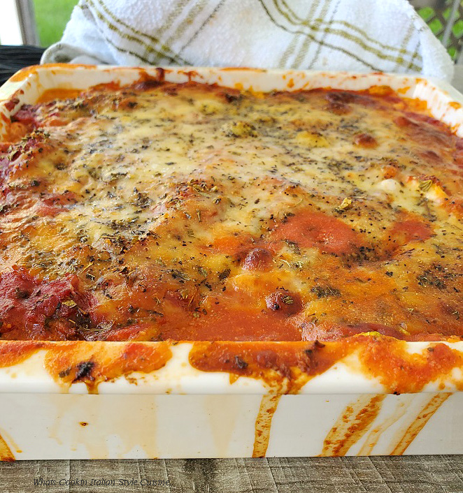 this is a casserole with browned mozzarella cheese on top and the casserole is made with zucchini and ricotta cheese inside