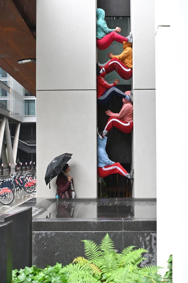 """Cenas bizarras à medida que as pessoas se empilham em """"esculturas corporais humanas"""" em Londres"""