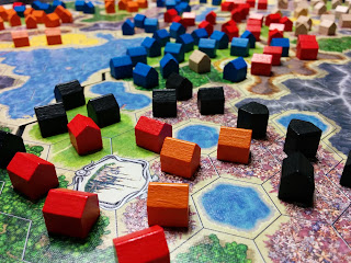 A close-up view of a game after it has ended. There are four sections of the game board, each placed together to form the play area. Each one is made up of a grid of hexagonal spaces, coloured to represent grasslands, forests, flowers, canyons, mountains, lakes, and deserts, with a fancy space representing a city. On most of the non-water spaces is a wooden house token in one of five colours: blue, white, black, red, and orange.
