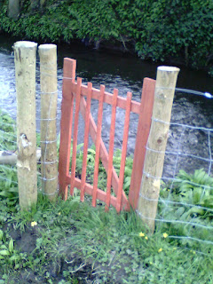 Small gate on river bank in the orchard.
