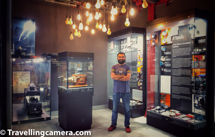 "A visit to Museo Camera, a museum dedicated to the history of cameras and photography, was long pending. Ever since it opened in the beginning of this year, VJ and I had talked often about it. Museo Camera, India's first not-for-profit, crowd-funded Center for Photographic Art, is an inspiring story in itself. Aditya Arya's years of hard work, dedication, and passion to the field of photography have culminated in the creation of this magical space.   The museum, earlier located in the basement of Aditya Arya's home, has now shifted to this beautiful building that is a fine specimen of strong, industrial architecture. Built around a mesh of sturdy, exposed iron beams, the museum is a sight to behold. And we have not even started talking about the content yet.   Located in one of the prime addresses of Gurgaon, DLF Phase 4, Museo Camera houses over 1500 cameras and 100s of other photography equipment such as apertures, light meters, artificial lighting equipment from various eras and was created through citizen funding. One of the most remarkable galleries in the museum is the one that covers the history of photography spanning across more than 200 years and a history of cameras.   The gallery starts with a prototype of Camera Obscura. The word Camera Obscura is latin and literally means the dark room. Mr Arya told us the that the word Camera was earlier spelled with a ""K"". So it was ""Kamera"". The urdu word ""kamra"" probably has the same origin. Languages are really interesting, aren't they?   Anyhow, the original Camera Obscura used to be as large as a room. The one in the Museum is a small box just to demonstrate how the original equipment used to work. Basically the basis is a natural optical phenomenon known as the pinhole image. When a scene outside a tent or a wall is projected on the otherside through a small opening, it appears reversed. This kind of a projection was earlier used for creating sketches and to study solar eclipse without damaging the eyes.   Then you come across the founding fathers of photography - Nicéphore Niépce, Louis-Jacques Mandé Daguerre, Sir John Hershel, and Louis Daguerre. You start with how Niepce created the first photograph and then learn about Dagerreotype, the photography technique created by Louis-Jacques Mande Daguerre. You find out how photography was so named, and then how the art of creating negatives was developed to ensure that photographs could be reproduced.   You walk along a huge wall that talks about the history of photography and the major contributors. Not only do you learn about the dates and pioneering companies such as Kodak, you also see several original photographs clicked by some very old cameras. You find out about photographers who have made significant contributions to the world of photography.   If you look closely, you will also find treasures such as original old advertisements and how they have evolved. You come across cameras of various shapes and sizes. You also see a hint of how studios were set up earlier. Another interesting fact that Mr Arya shared with us was about the portraits that were clicked during Victorian times. Mr. Arya has sourced them from auctions, flea markets, etc over the years.   If you have seen some of these portraits you would notice the lack of smiles and a passive expression in the subjects. The reason for that was that at those times, since aperture was very small, the exposure needed to be larger and as a result slightest of movements would blur the images. Therefore subjects were asked to strike a natural pose that would be easy to hold for 15 seconds or so.   The ground floor houses this interesting gallery and a shop from where you can buy mementos. There's also a cafe, called ""fig at museo"" that serves some delicious looking food, which we were unfortunately not able to sample today. But it looks like a cool and relaxed space.   The first floor houses exhibition halls where currently the Aravalli series is on display. Photographers can rent the space for their exhibitions here. It is a fairly large space and the infrastructure too is good. The place also gets good footfall from the right kind of audience.   The second floor has a classroom/conference hall where one can organize workshops or talks or other events. Apparently, there are four such spaces in the building. There's also a small library here where you can sit and read. You cannot rent out the books yet. That is still being figured out. In this space, amateur photographers can also put their work up for display and even sell it to walk-in customers.   Apart from this all, there's an amazing sign here that says ""Photography is strictly allowed"". It is such a warm and friendly place. Coming to the ticketing aspect of it, you need to pay Rs 200 per person, unless you are a founding member. We became founding members during the initial rounds of crowd sourcing. You can still become one. The information is available at the front desk.   Mr Aditya Arya has always been an inspiring person for us. We have followed his journey as a photographer very closely. Apart from that, we also visited his farm in the Aravallis where he has built a stone cottage all by himself. He was also at the helm of the Aravalli exhibition that was an attempt to put forth the plight of the Aravalli Ecosystem. And now Museo Camera. Mr Arya says that he is always working on something in parallel that may convert into something substantial in the long run. I think that is what sets him apart. And that is what makes him a visionary.    MUSEO CAMERA Shri Ganesh Mandir Marg, DLF Phase IV, Sector 28, Gurugram, Haryana 122002 Gurgaon, Haryana 122001 M: +91 8287814216"