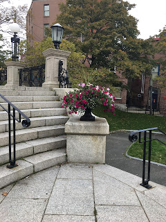 A large stone vase full of white, reddish-purple and purple flowers near the steps up to the Newfoundland War Memorial. Some of the steps are visible on the left side of the photo.