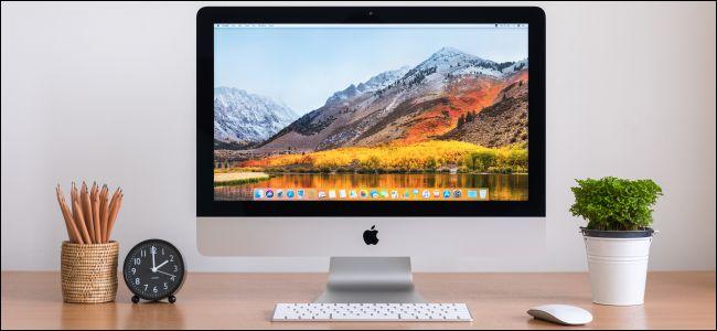 جهاز iMac مع لوحة مفاتيح Apple وماوس على مكتب خشبي.