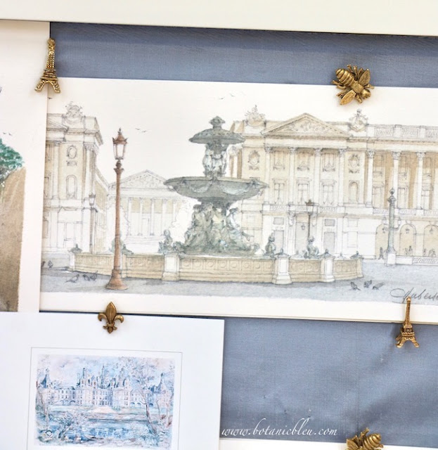 Add pizzazz to a shadowbox by using 3-D gold Eiffel tower, fleur de lis, and bee tacks tacks