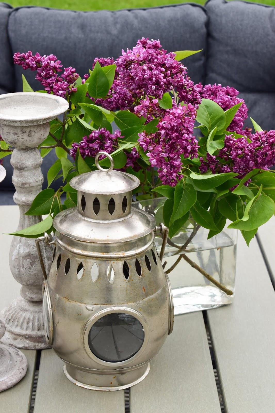 Deko mit Flieder für deinen Gartentisch. Dekoidee Garten Outdoor Möbel mit Flieder Laterne Kerzenständer. Naturdeko