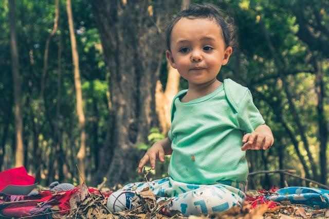 Criança sentada em pano de piquenique