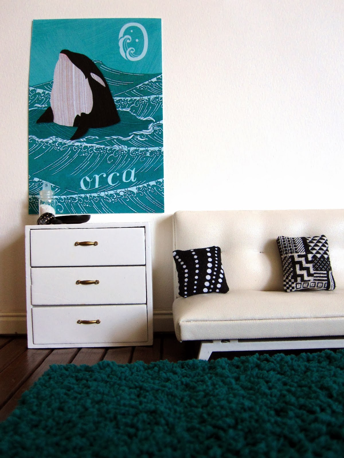 Modern dolls' house lounge room with teal flokati rug, white sofa and drawers, black and white cushions and orca art poster