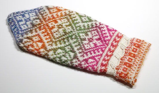 Back of hand knit wool colorwork mitten on a white background.
