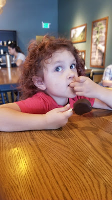 Little girl with curly brown and pink-ish hair and sapphire eyes, sitting at a high top table in Starbucks, eating a chocolate cake pop