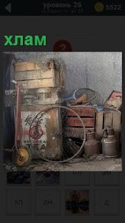 В углу сложен различный хлам. Это старое колесо, разбитые деревянные ящики, бидоны и другая утварь