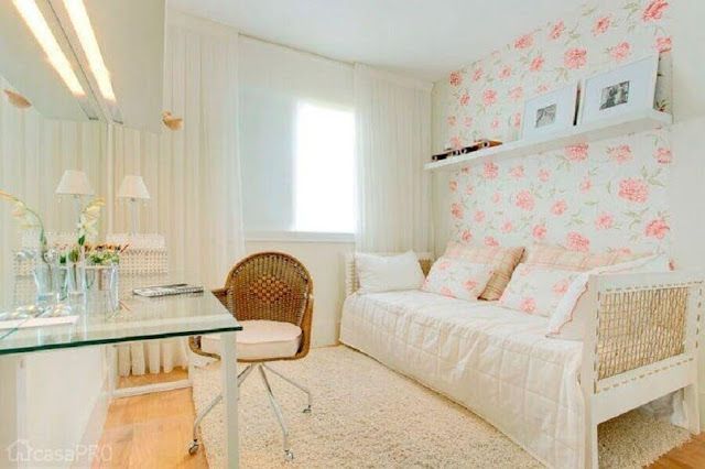 Young female bedroom decoration in light tones and with delicate wallpaper
