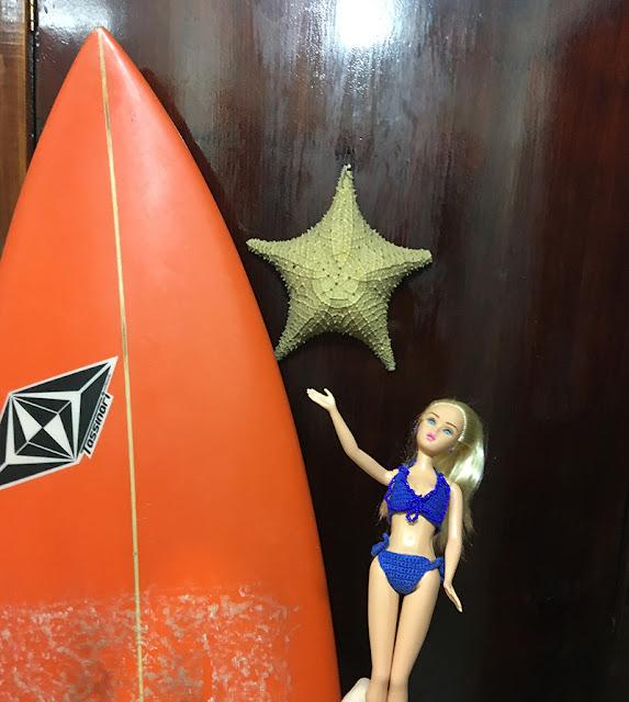 Susi com uma enorme prancha de surfe laranja