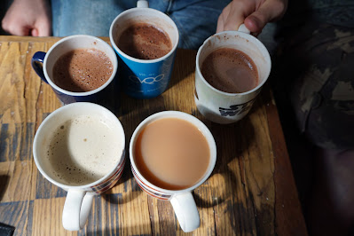 5 mugs in a circle on a table with different hot drinks