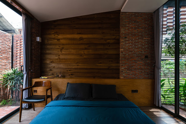 mix of brick and wood paneling at head of bed