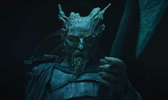 Imagem de capa: o Cavaleiro Verde, um humanóide com o rosto feito de madeira, uma barba e chifres feitos de madeira, usanso uma capa e segurando um machado.