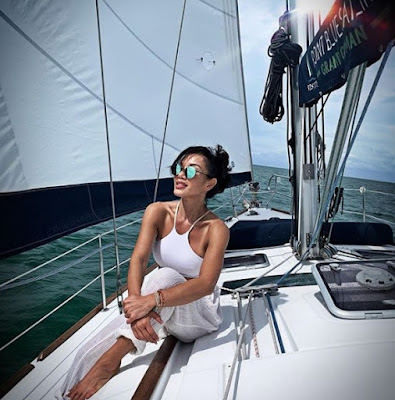 Sharon Tay sitting in a boat & enjoying traveling
