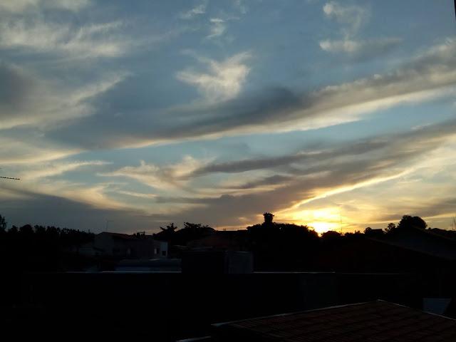 Imagem do por sol em meio a nuvens carregadas