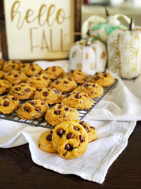 pumpkin chocolate chip cookies on a cooling rack in front of fall decor
