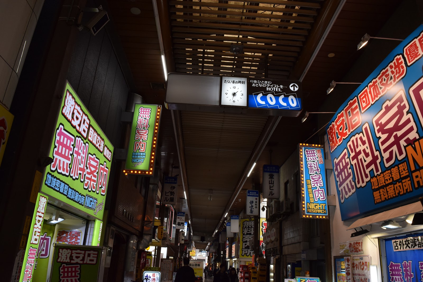 Covered shopping street in Osaka with neon signs saying muryo annnaijo