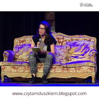 Paula siedzi na stylizowanej kanapie. w dłoniach trzyma tomik wierszy i mikrofon, opowiada o swojej twórczości.