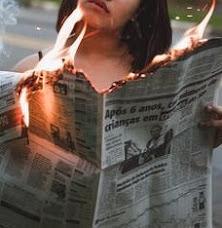 女性が燃える新聞を手に取って見ている