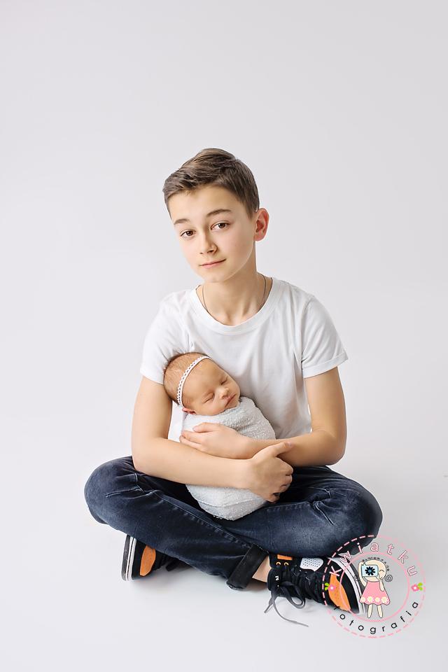 Nastoletni brat trzyma swoją nowonarodzoną siostrzyczkę